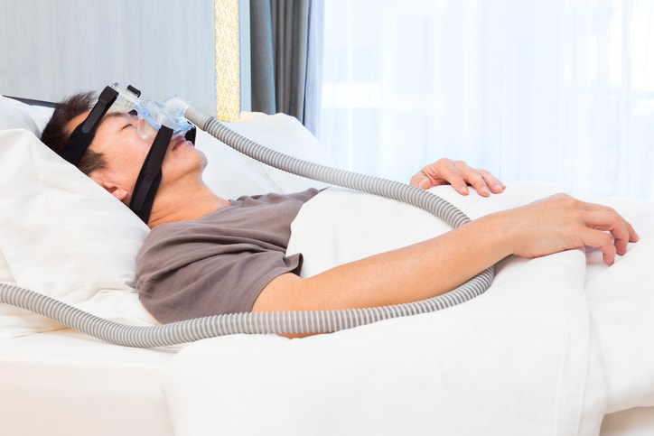 man sleeping in bed with CPAP mask